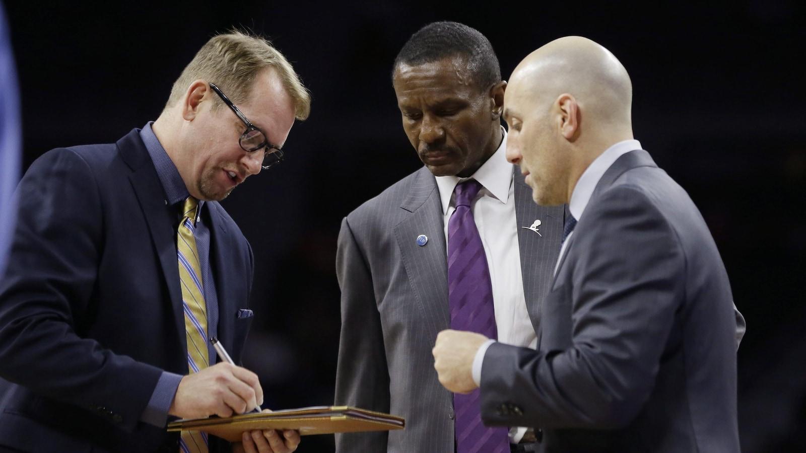 Nick Nurse, tableau et stylo en mains, parle stratégie avec Dwane Casey et Rex Kalamian.