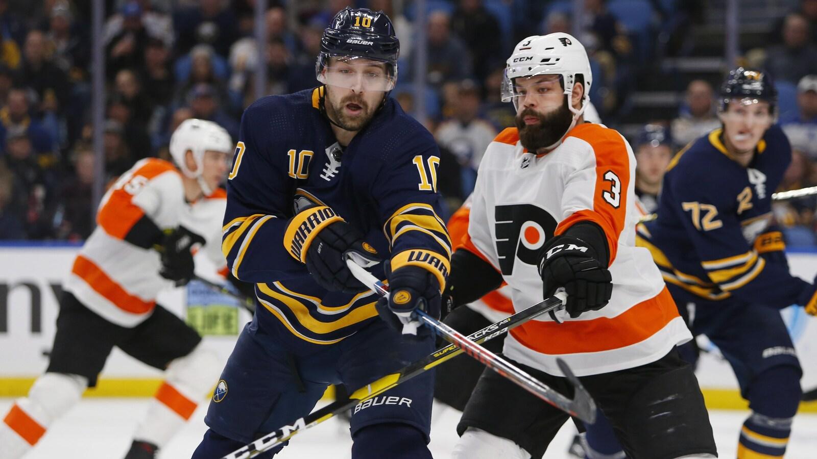 Patrik Berglund tient le bâton de Radko Gudas en échec pendant un match entre les Sabres et les Flyers de Philadelphie à Buffalo.