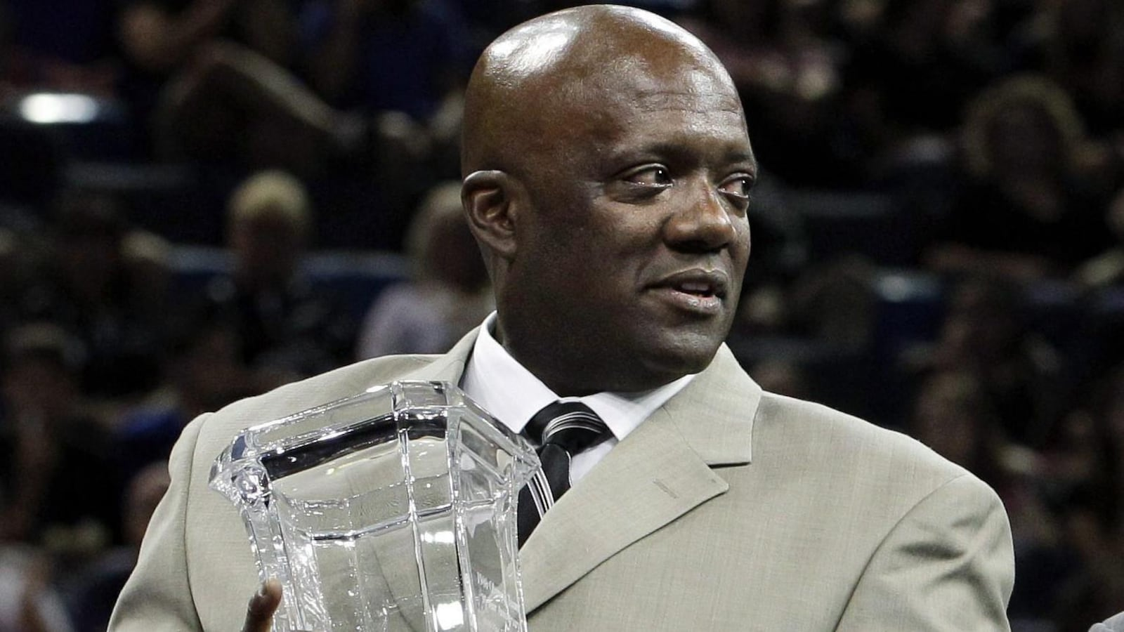 Il tient un trophée en verre.