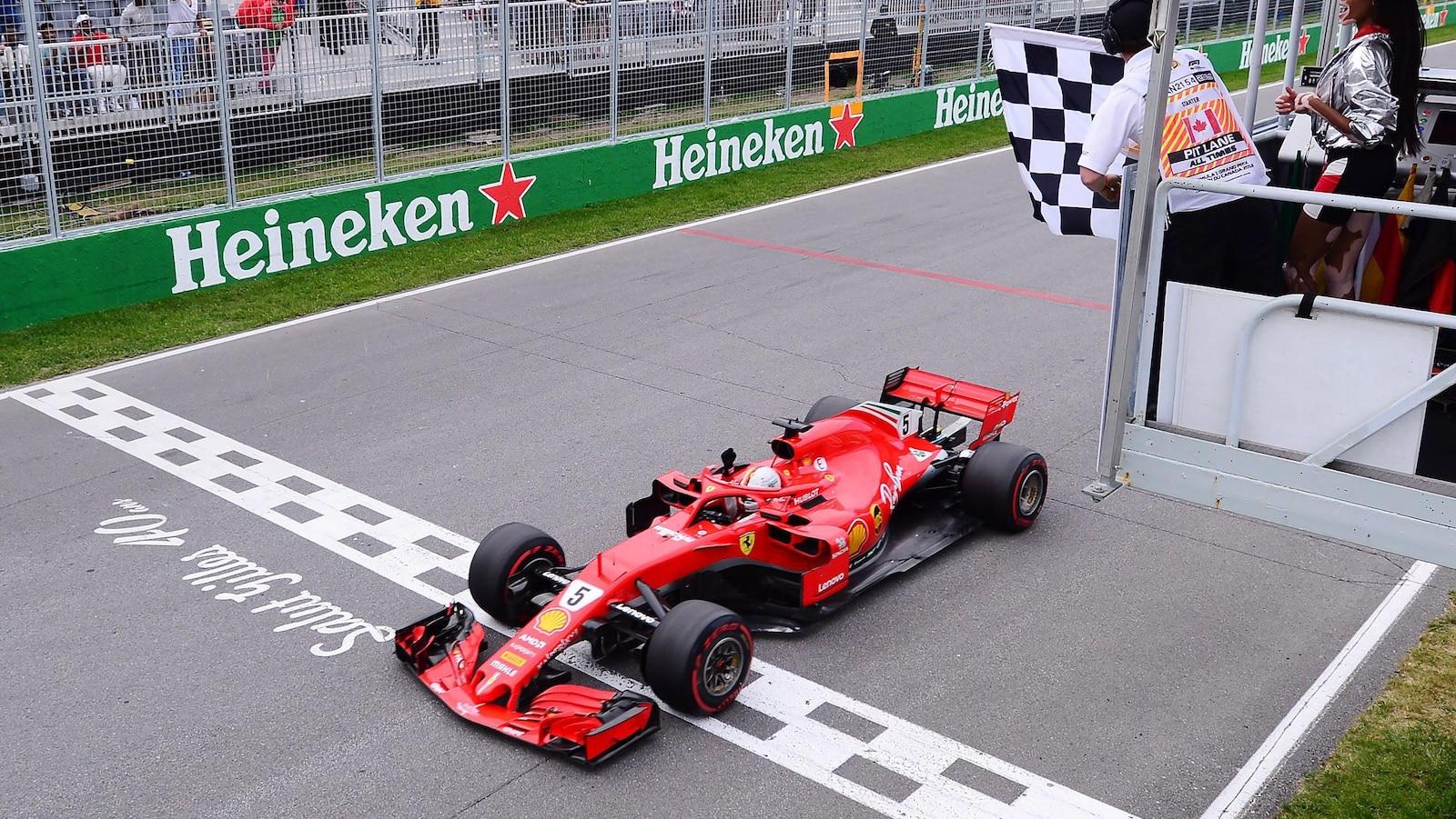 Le pilote Ferrari traverse la ligne d'arrivée sous le drapeau à damier pour remporter le Grand Prix