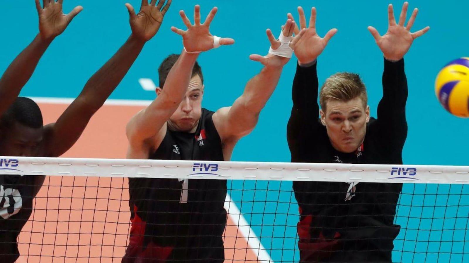 Des joueurs canadiens sautent pour bloquer un smash.