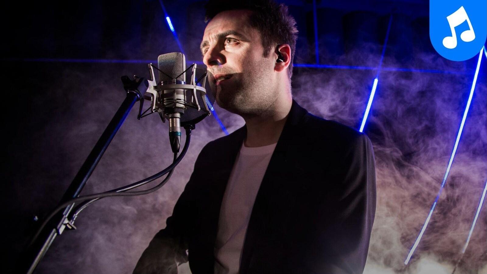 Dumas en prestation solo, chante au micro, une guitare Gibson dans les mains.
