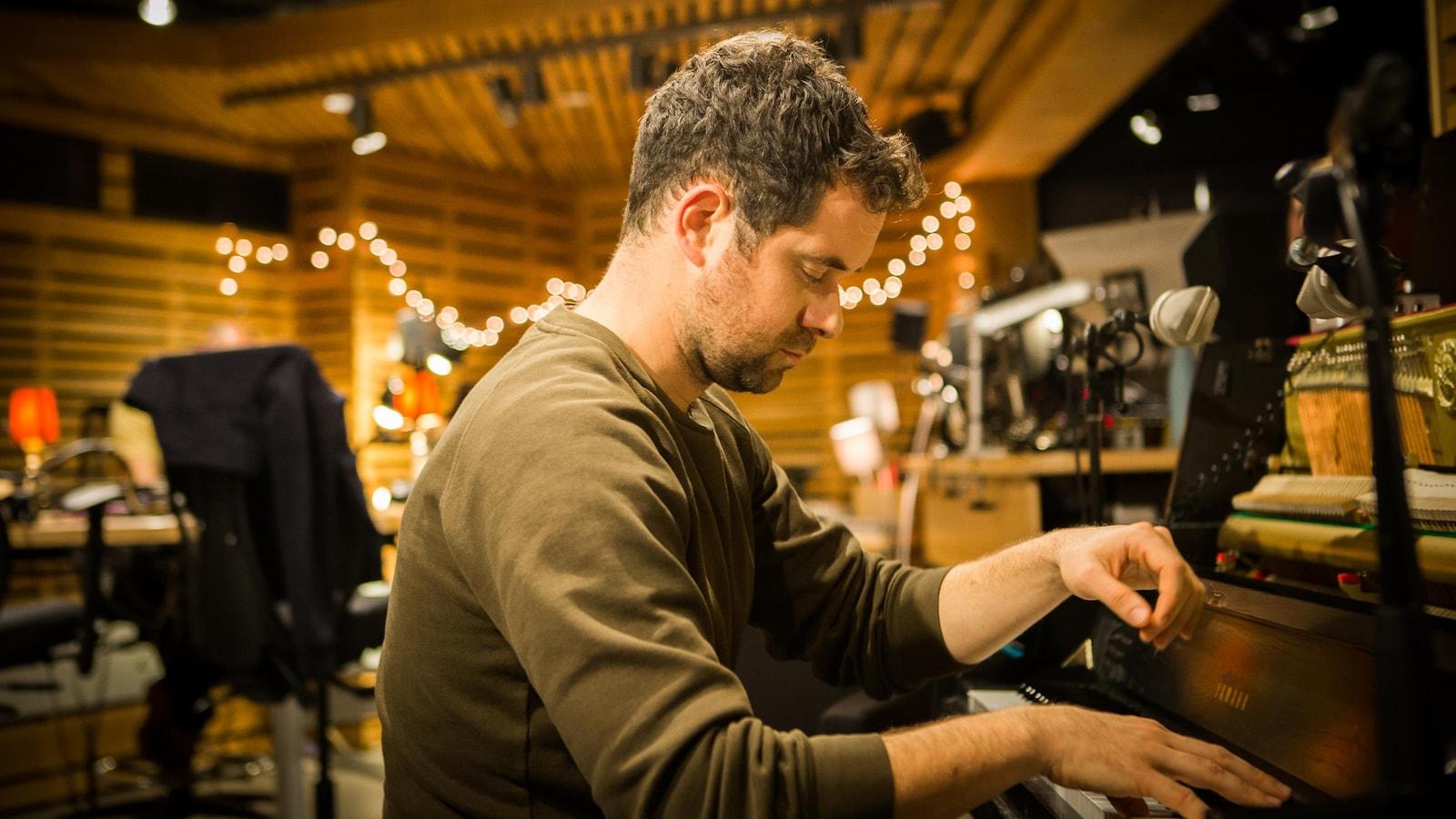 L'artiste, de profil, est en train de jouer du piano d'un air très concentré.