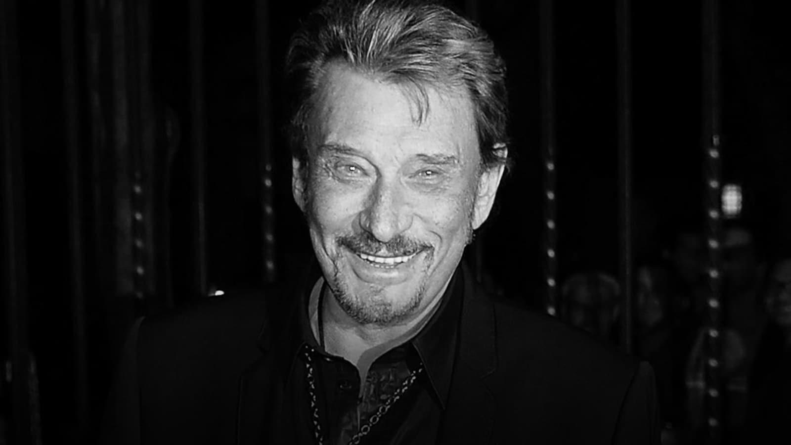 Une photo en noir et blanc du chanteur qui sourit