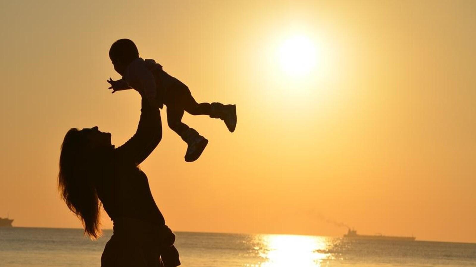 Une mère qui lève son bébé dans les airs devant un coucher de soleil.