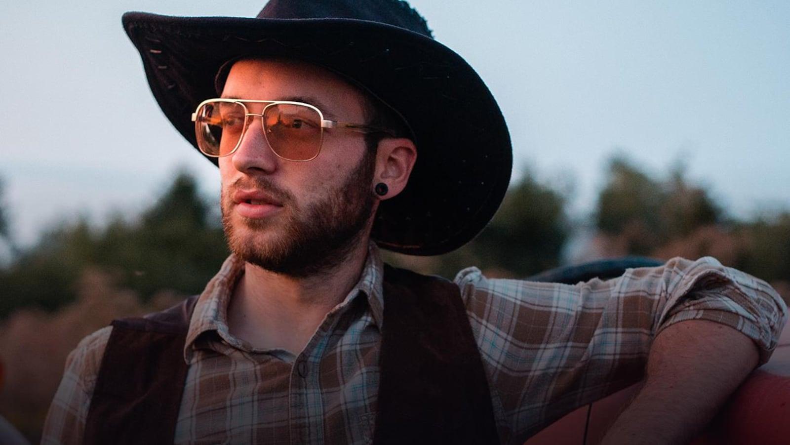 Menoncle Jason, lunettes de soleil, chapeau de cowboy et chemise à carreaux, le bras gauche appuyé sur une camionnette rouge.