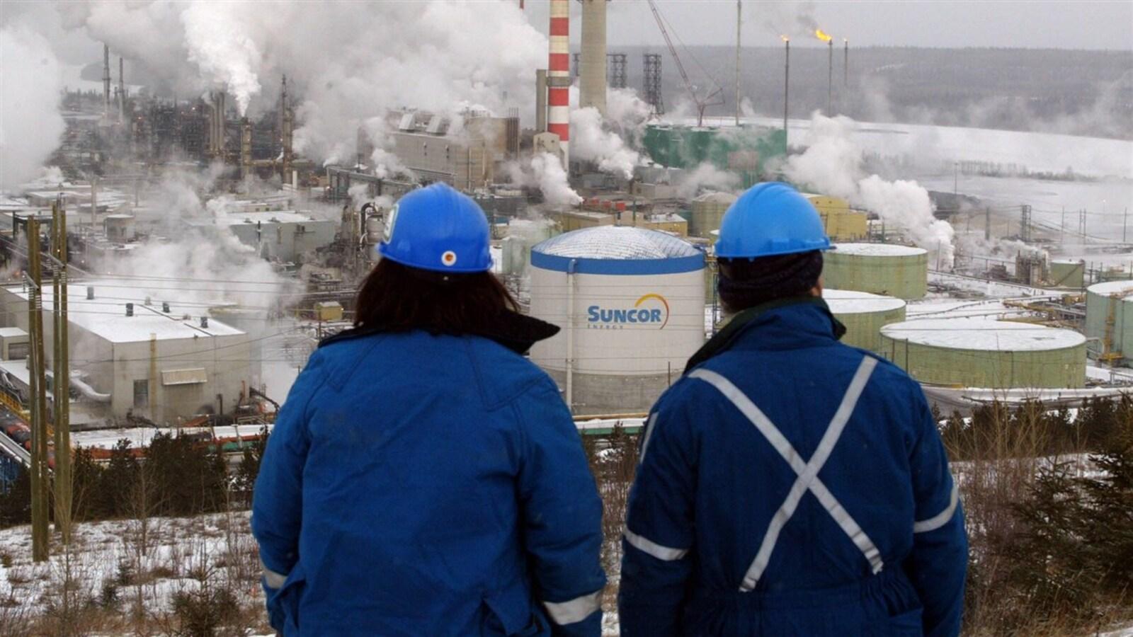Des ouvriers observent au loin l'usine de Suncor.