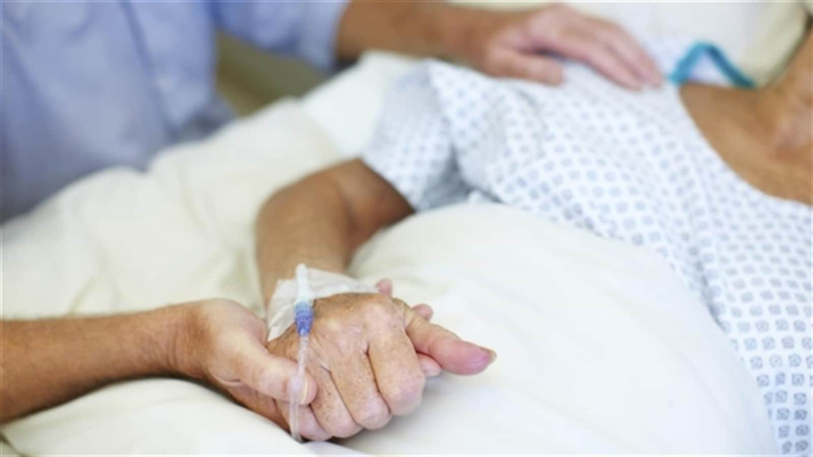 Quelqu'un tient la main d'un patient alité portant une jaquette d'hôpital.