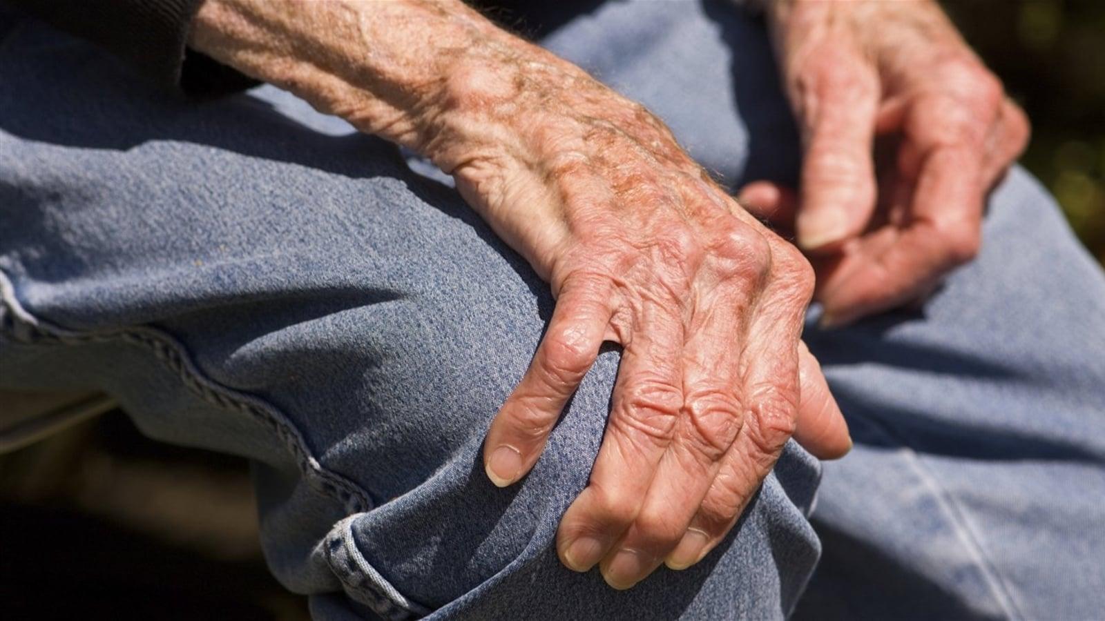 La main d'un vieil homme déposée sur son genou
