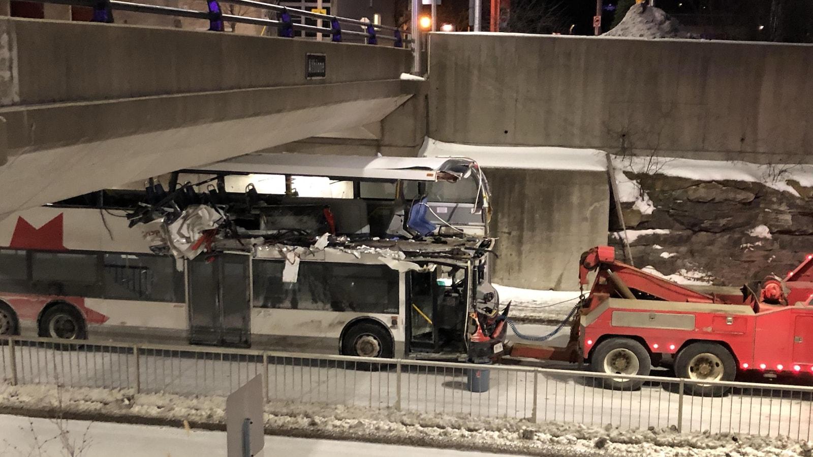 Un autobus accidenté se fait remorquer.