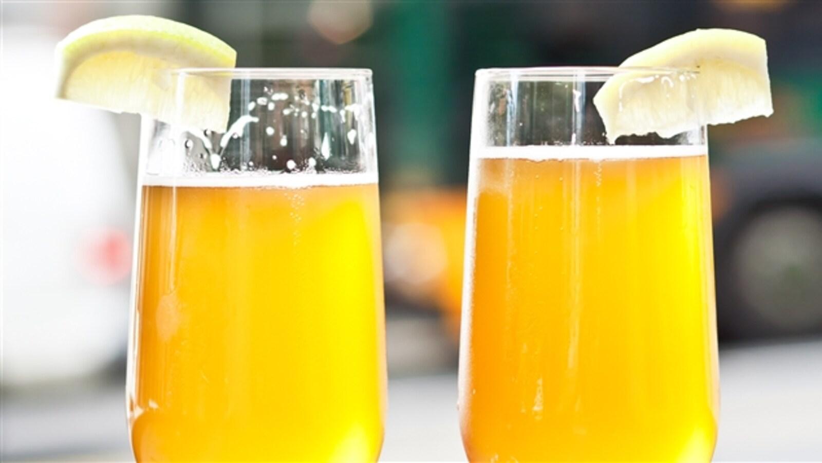 Des verres remplis de bières accompagnés de tranches de citron.