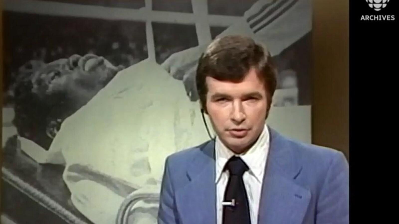 L'animateur Michel Benoît présente un reportage sur l'état de santé de Cleveland Denny.  Dans une mortaise à l'arrière de l'animateur, il y a une image de Cleveland Denny couché dans une civière.