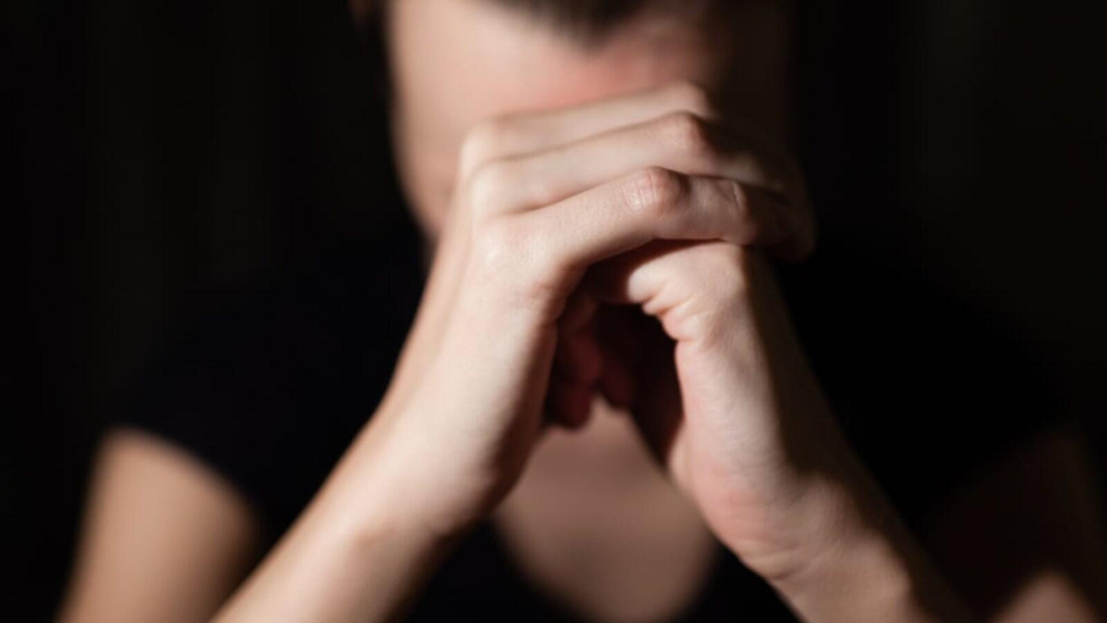 Une femme a le visage caché par ses mains croisées.