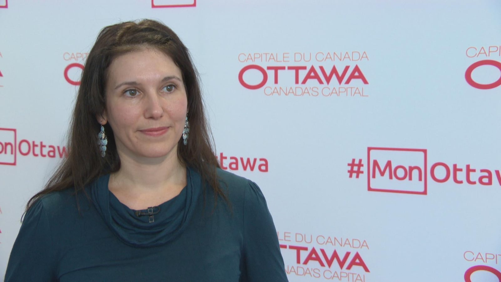 Catherine Callary en entrevue devant un fond blanc portant l'inscription « capitale du Canada, Ottawa ».