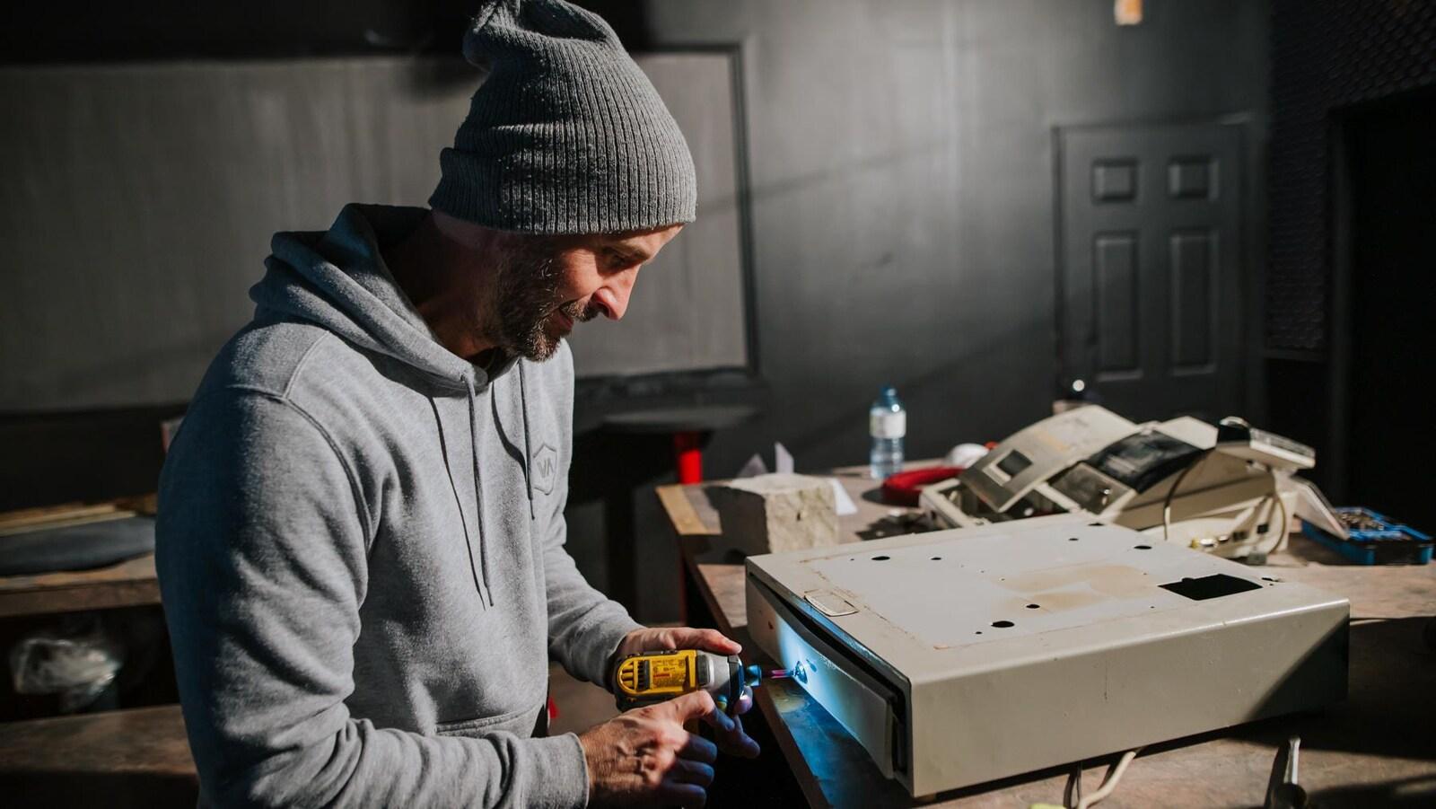 Un homme travaille à la réparation du tiroi- caisse d'un bar.