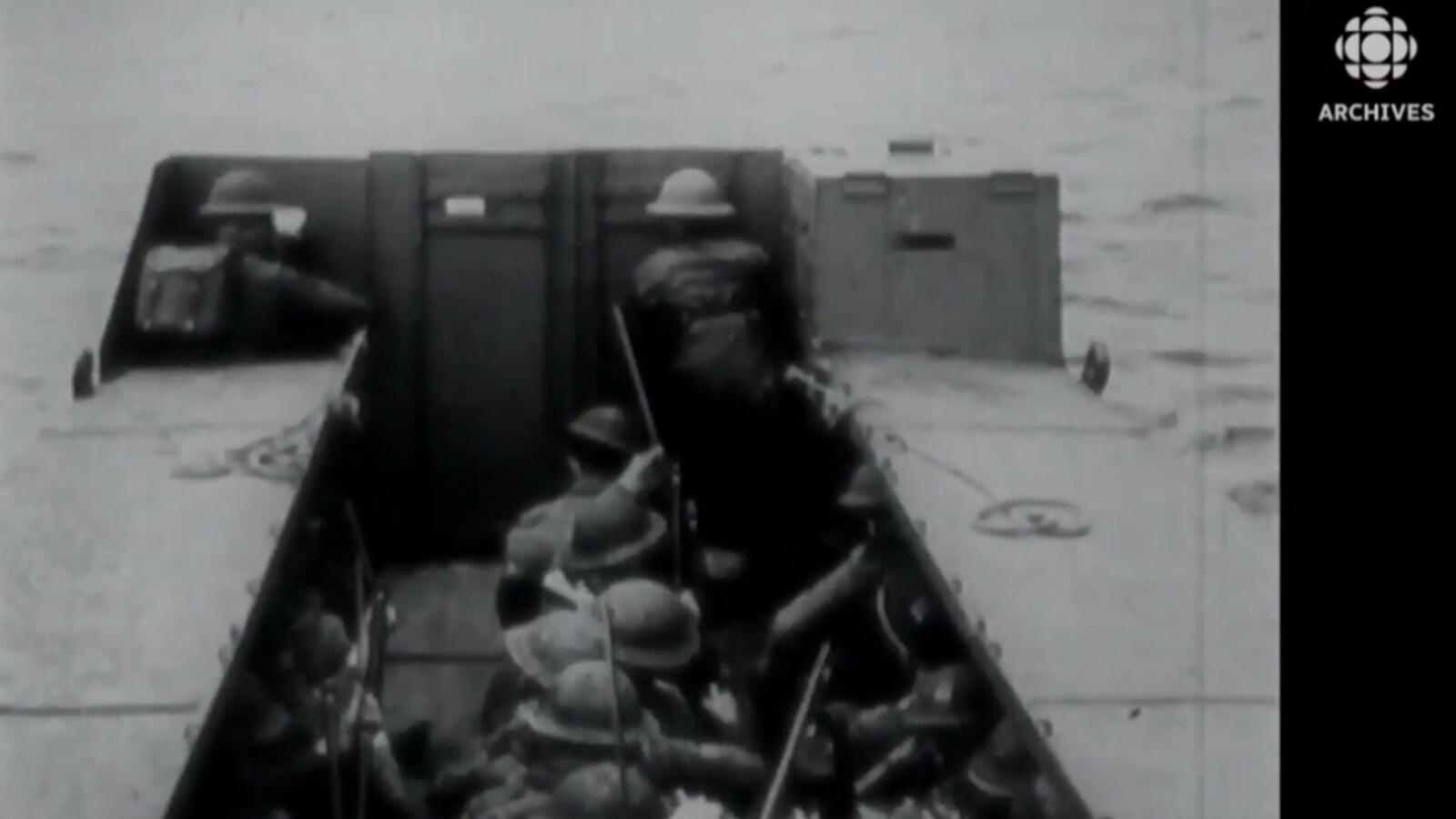 Des soldats dans une péniche s'approchent de la côte normande.
