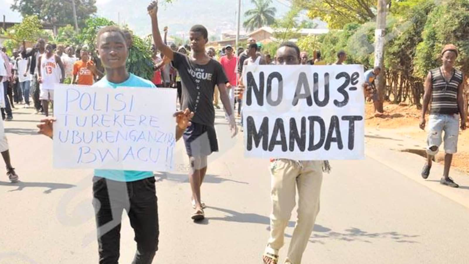 Un jeune manifestant tient une pancarte sur la quelle il est écrit : No au 3e mandat.