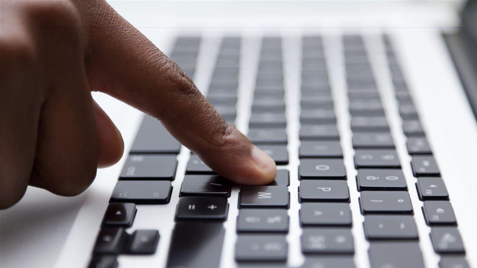 Gros plan sur une main dont un doigt appuie sur une touche de clavier d'ordinateur.