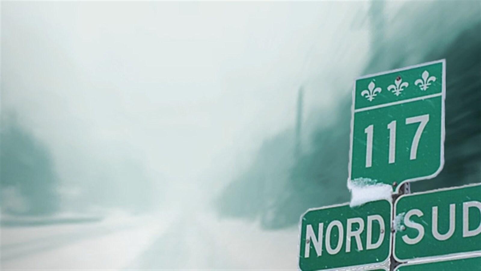 Panneau indicateur de la route 117 devant une route dans le brouillard