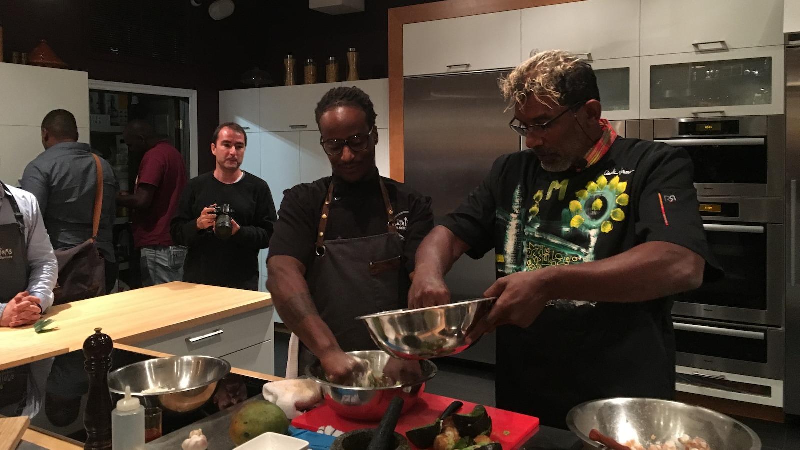 Le chef  martiniquais Guy Ferdinand en cuisine. Il travaille avec un assistant sous le regard des journalistes