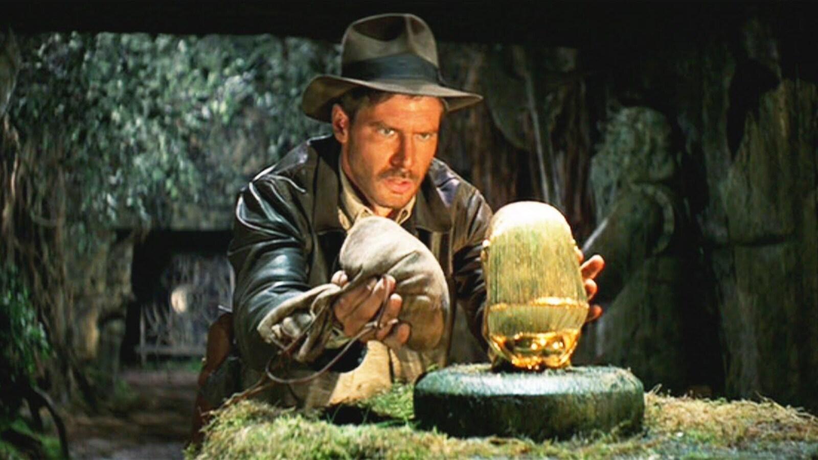 Indiana Jones s'empare d'un objet d'art dans une scène du film Les aventuriers de l'arche perdue (1981).