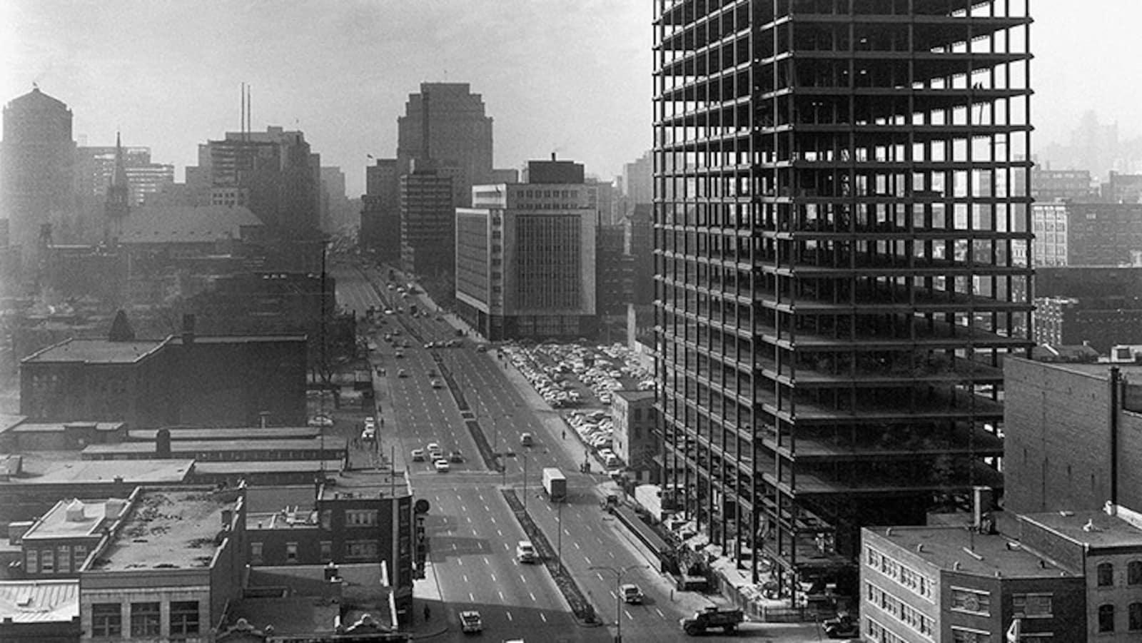 Vue panoramique de l'édifice et de ses grues avec les autres édifices montréalais en arrièrre-plan.