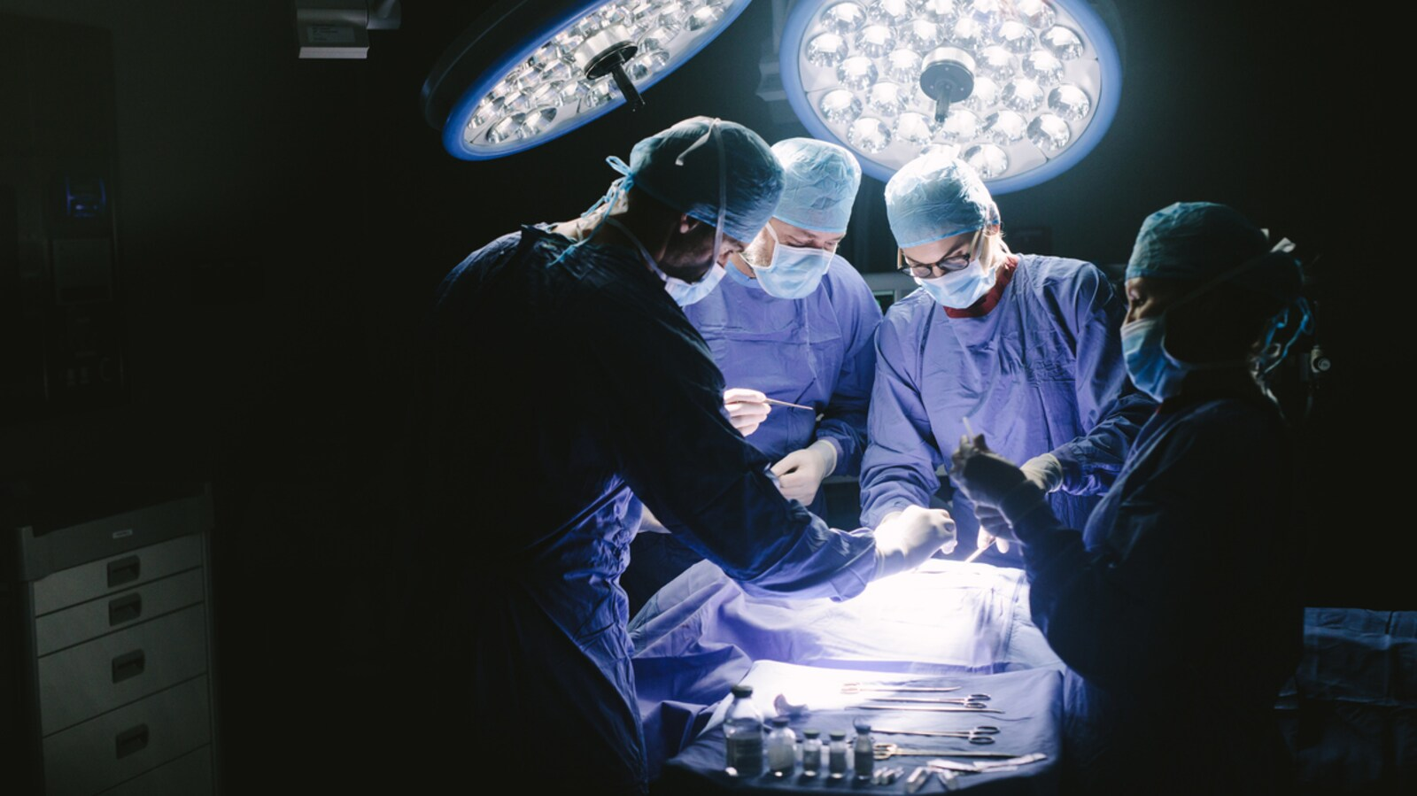 Vue générale d'une salle d'opération avec quatre membres d'une équipe médicale à l'oeuvre.