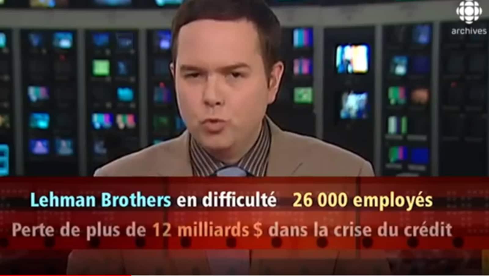 Le journaliste Gérald Fillion devant un mur d'écrans explique l'impact de la faillite de la banque Lehman Brothers.