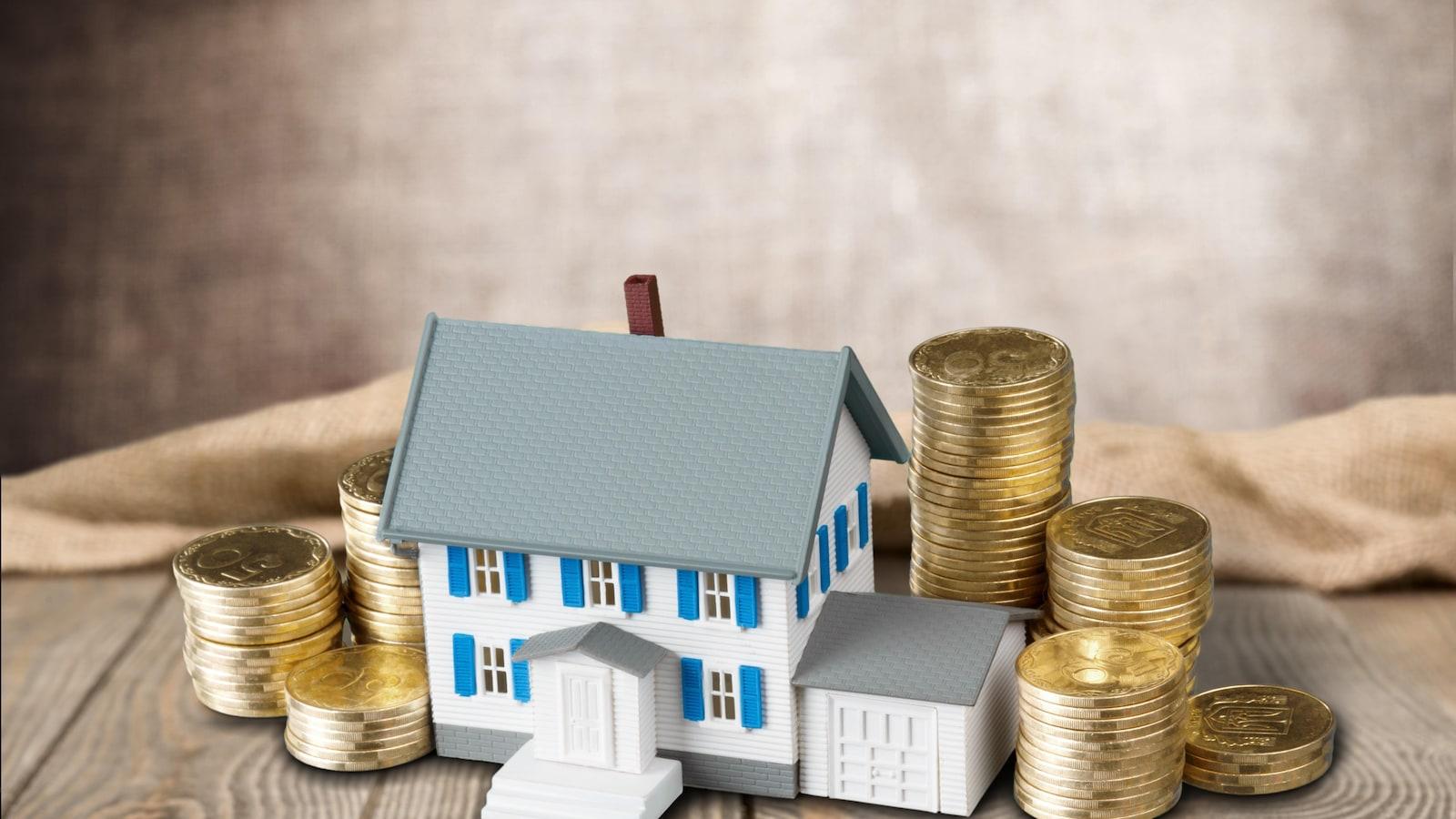 Une maison miniature est entourée de pièces de monnaie.
