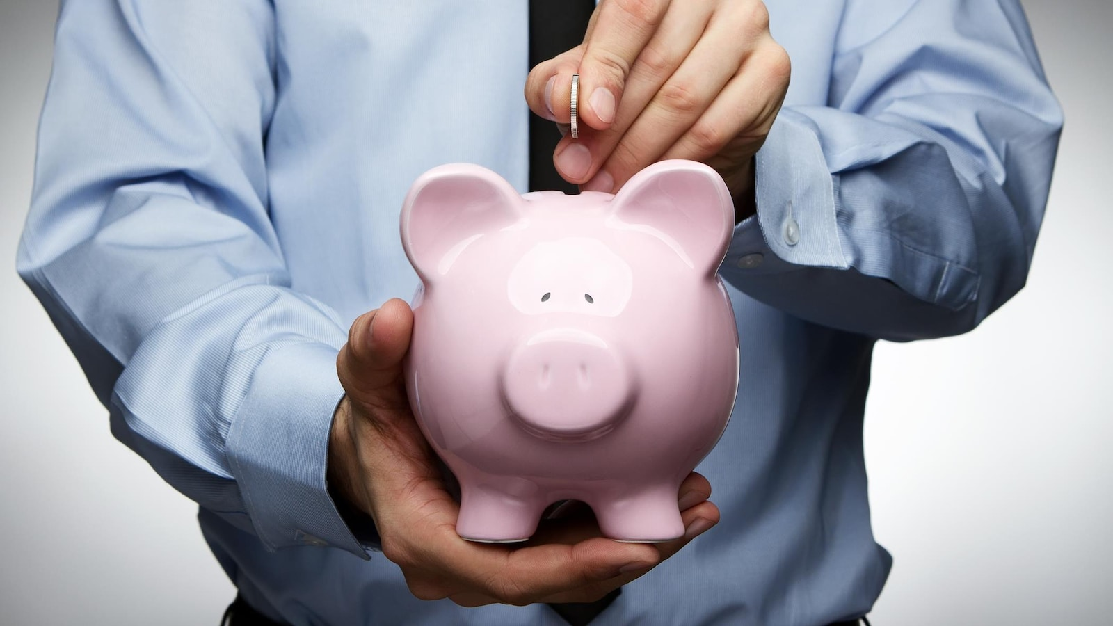 Un homme en cravate dépose un sou dans une tirelire en forme de cochon qu'il tient dans sa main.