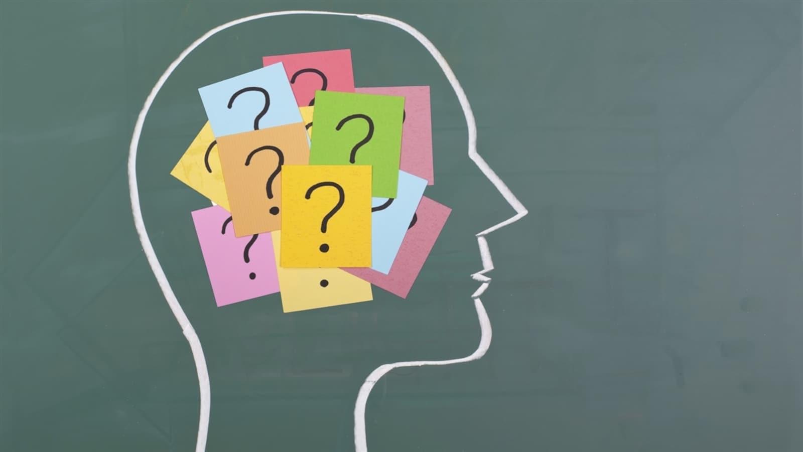 Dessin à la craie d'un cerveau avec des bouts de papier marqués d'un point d'interrogation