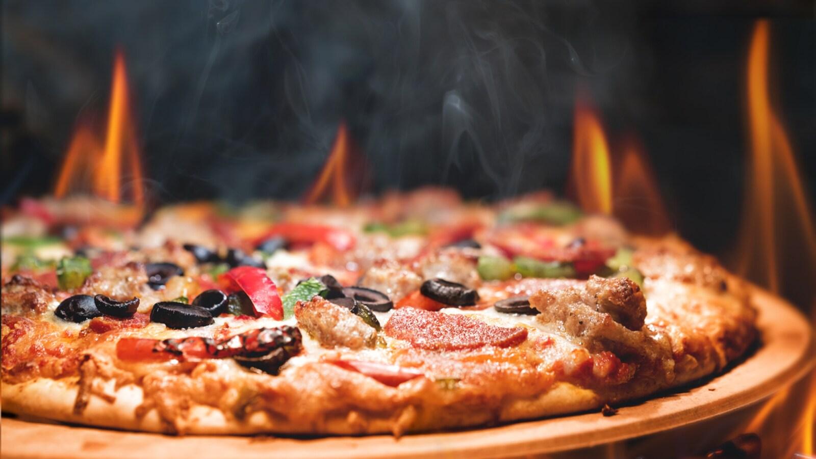 Une pizza dans un four, avec des flammes.