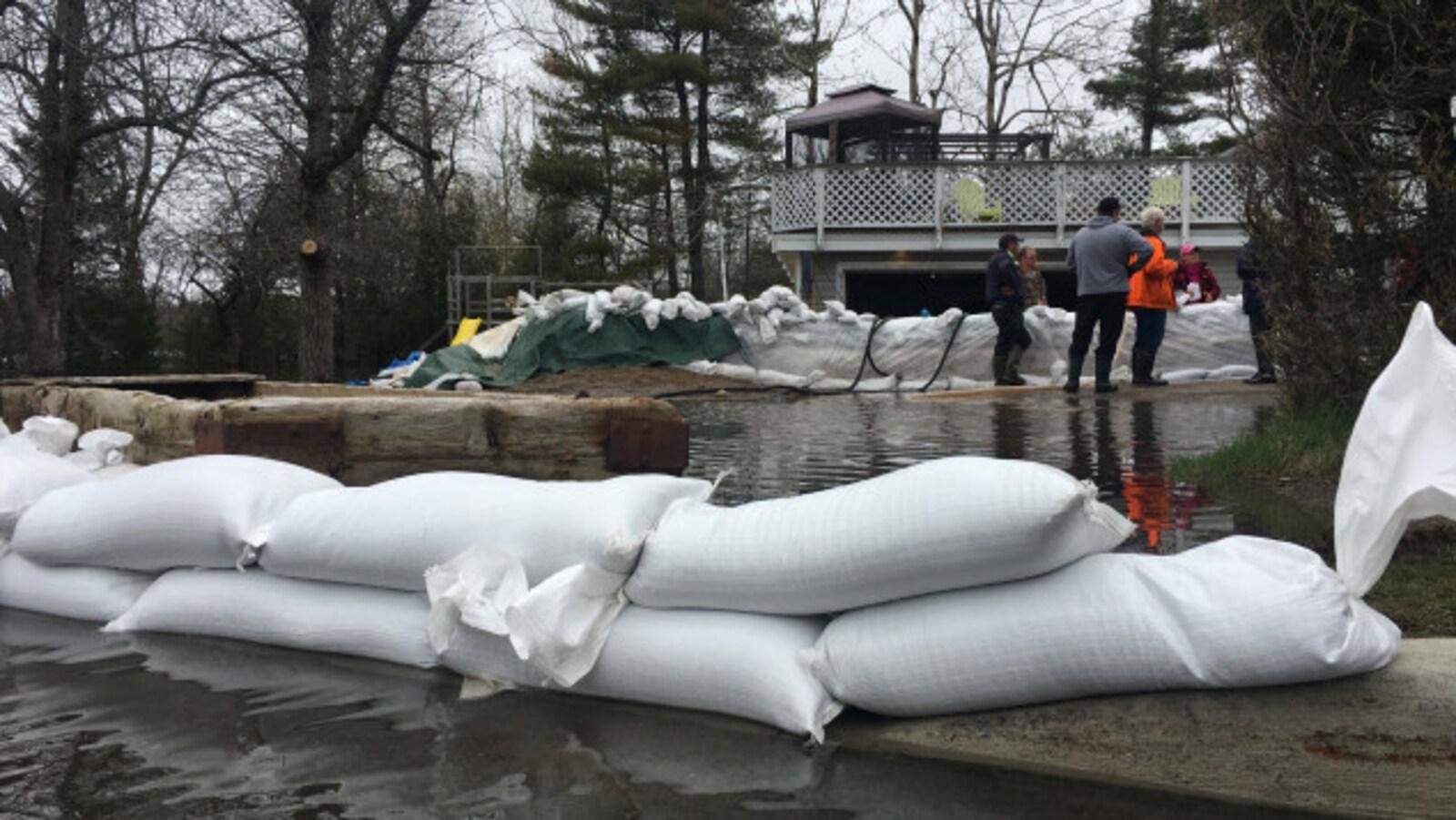 Plusieurs résidents tentent de limiter les dégâts avec des sacs de sable au printemps 2018, comme ces citoyens de Saint-Jean, au Nouveau-Brunswick.