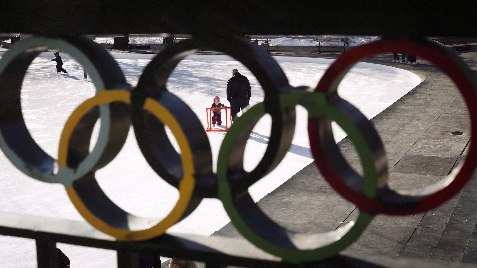 On l'entrevoit au travers des anneaux olympiques.