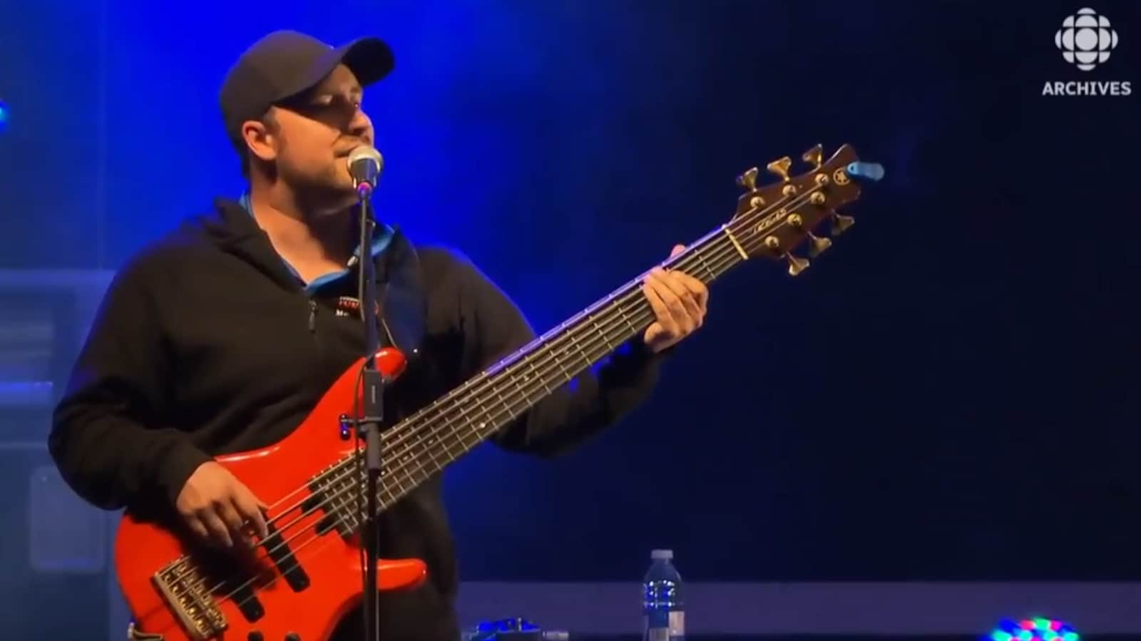 Le chanteur Kim Fontaine joue de la basse à six cordes lors d'un spectacle.