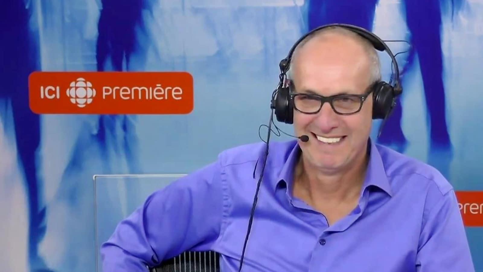 L'animateur Alain Gravel, souriant, dans son studio d'ICI Première.