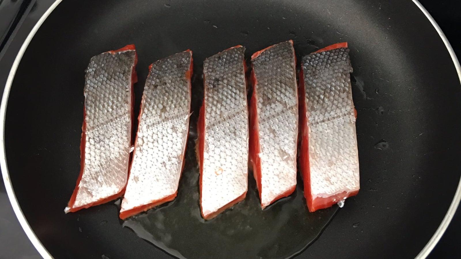 Du saumon qui grille dans un poêlon.