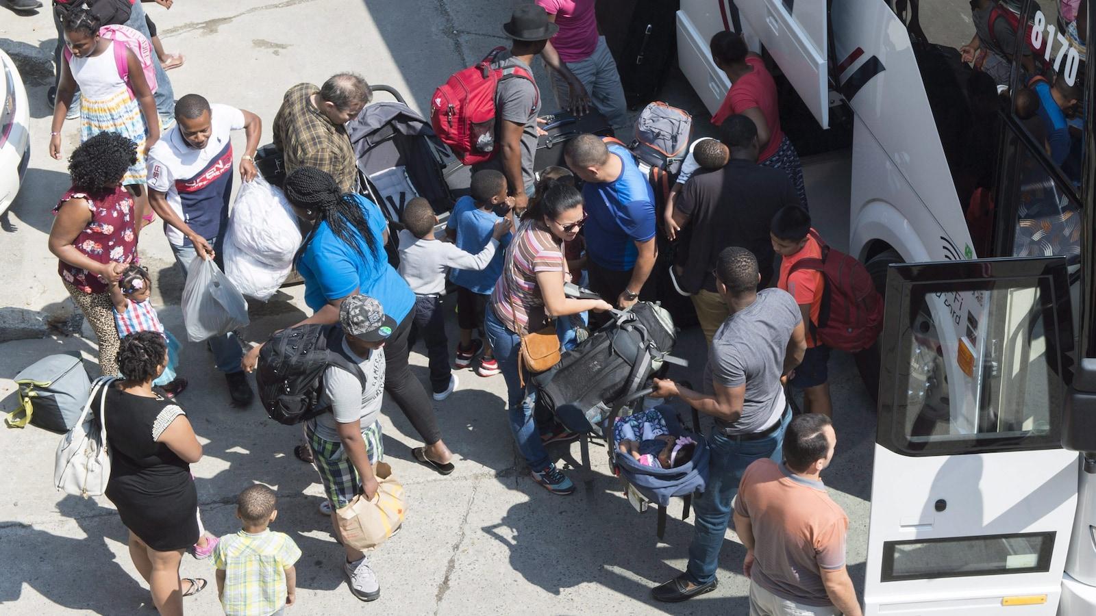 Des migrants arrivent au stade olympique de Montréal, où ils seront logés temporairement.