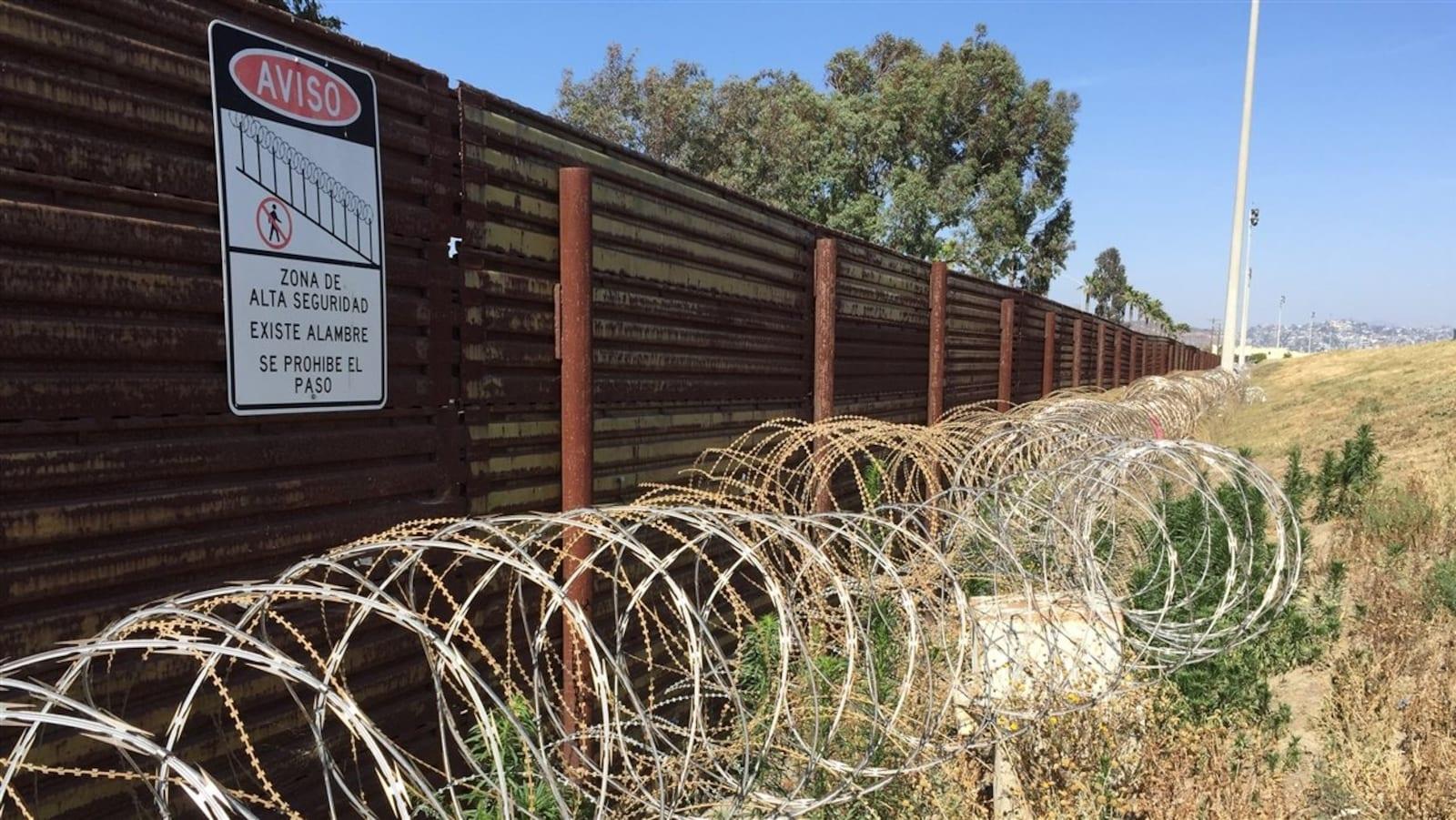 Un mur et des barbelés le long de la frontière entre les États-Unis et le Mexique.