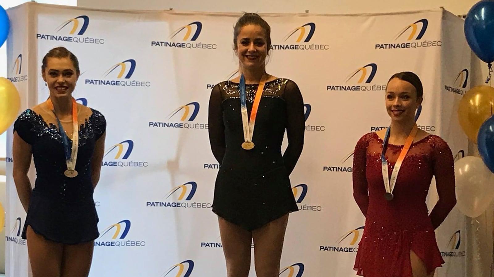Elle est sur le podium en compagnie des autres médaillées.