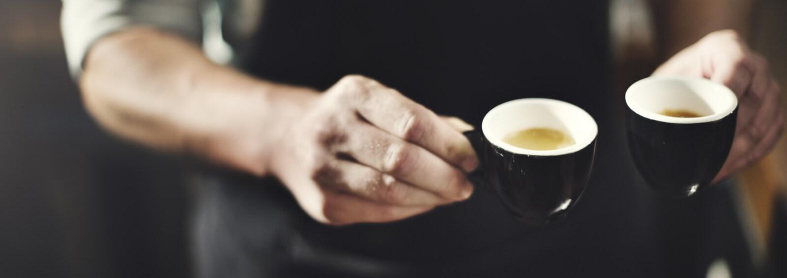 Gros plan sur les mains d'un serveur tenant deux petites tasses de café.