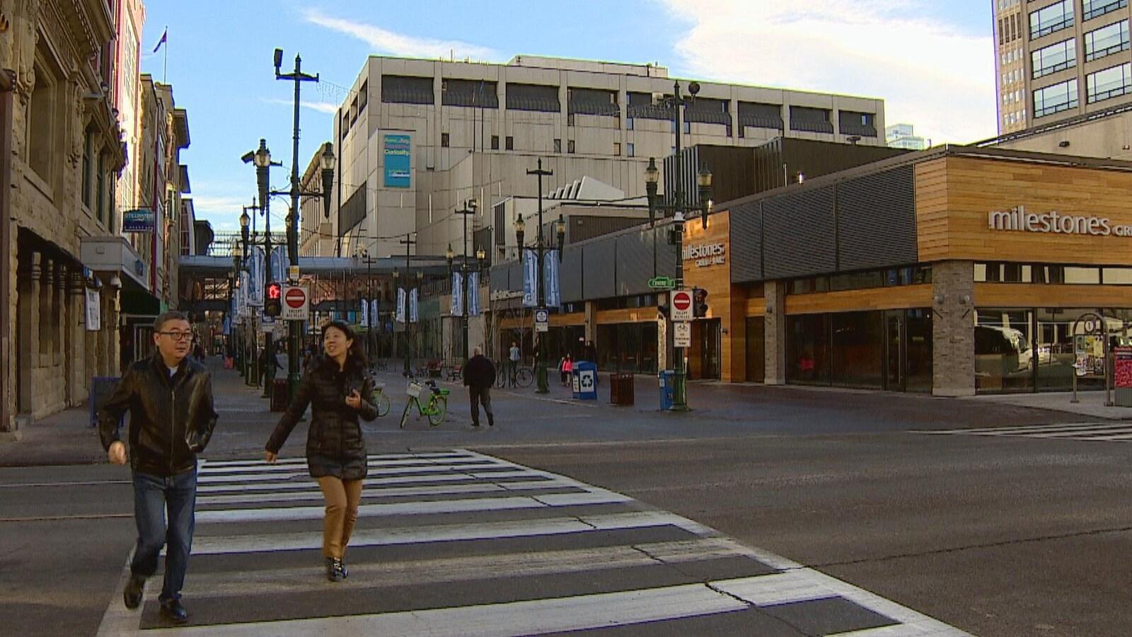 Deux personnes marchent dans une rue du centre-ville.