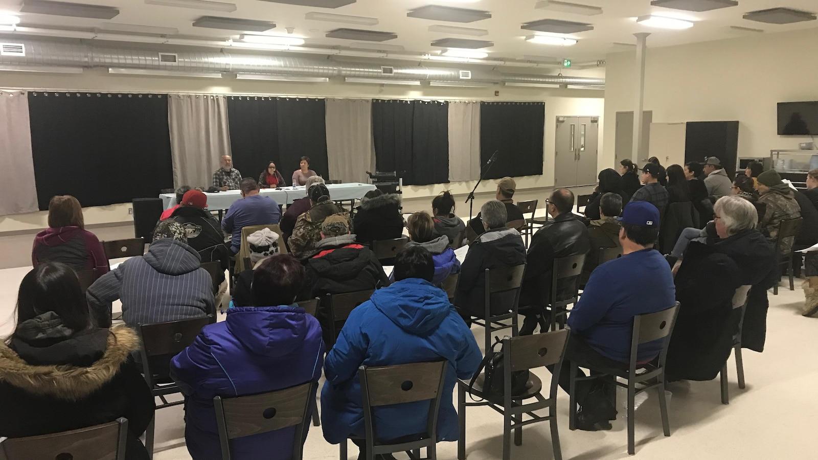 Une cinquantaine de personnes sont assis sur une chaise dans une salle en regardant 3 personnes qui parlent devant.