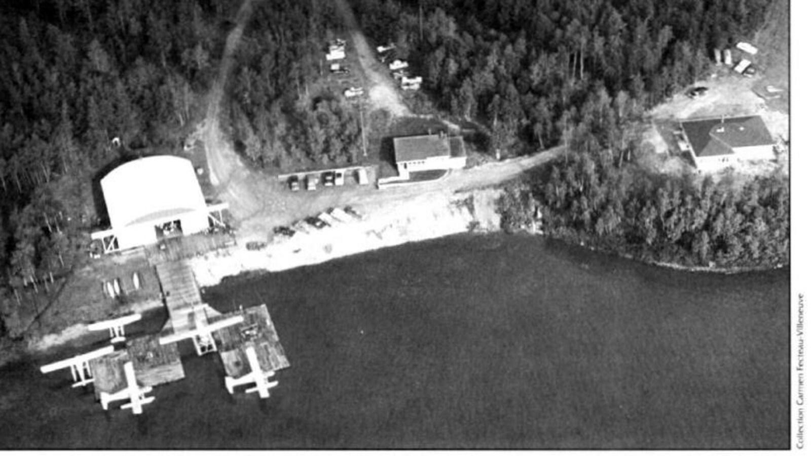 Une photographie d'archives en noir et blanc, montrant à vol d'oiseau, des bâtiments sur le bord de l'eau. De petits avions y sont amarrés.