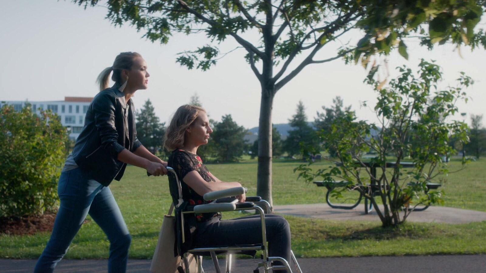 À l'extérieur, Julie Ringuette pousse la chaise roulante sur laquelle est assise Léane Labrèche-Dor.