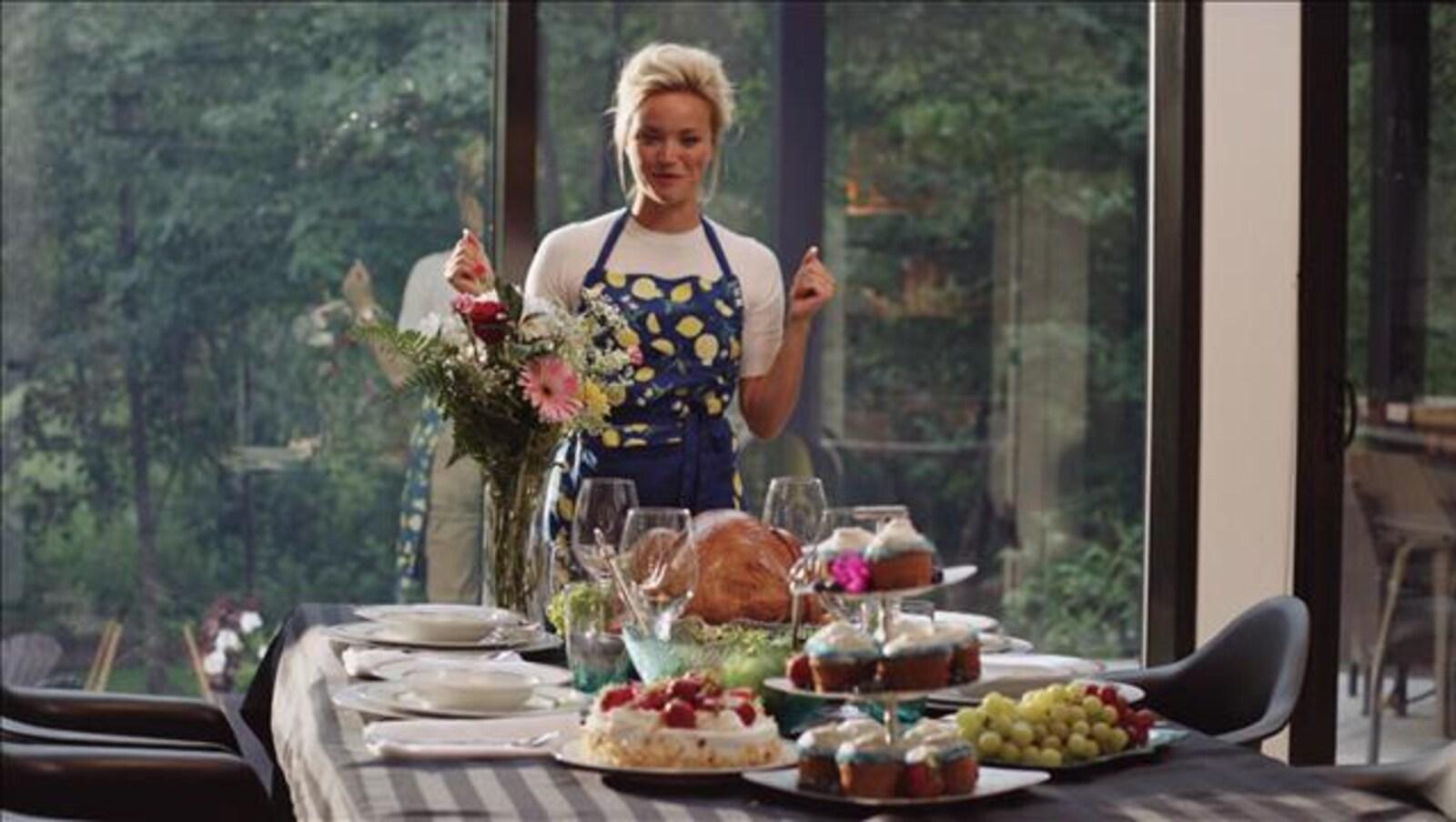 Souriant, le personnage interprété par Julie Ringuette regarde la table de cuisine occupée par de nombreux plats alléchants.