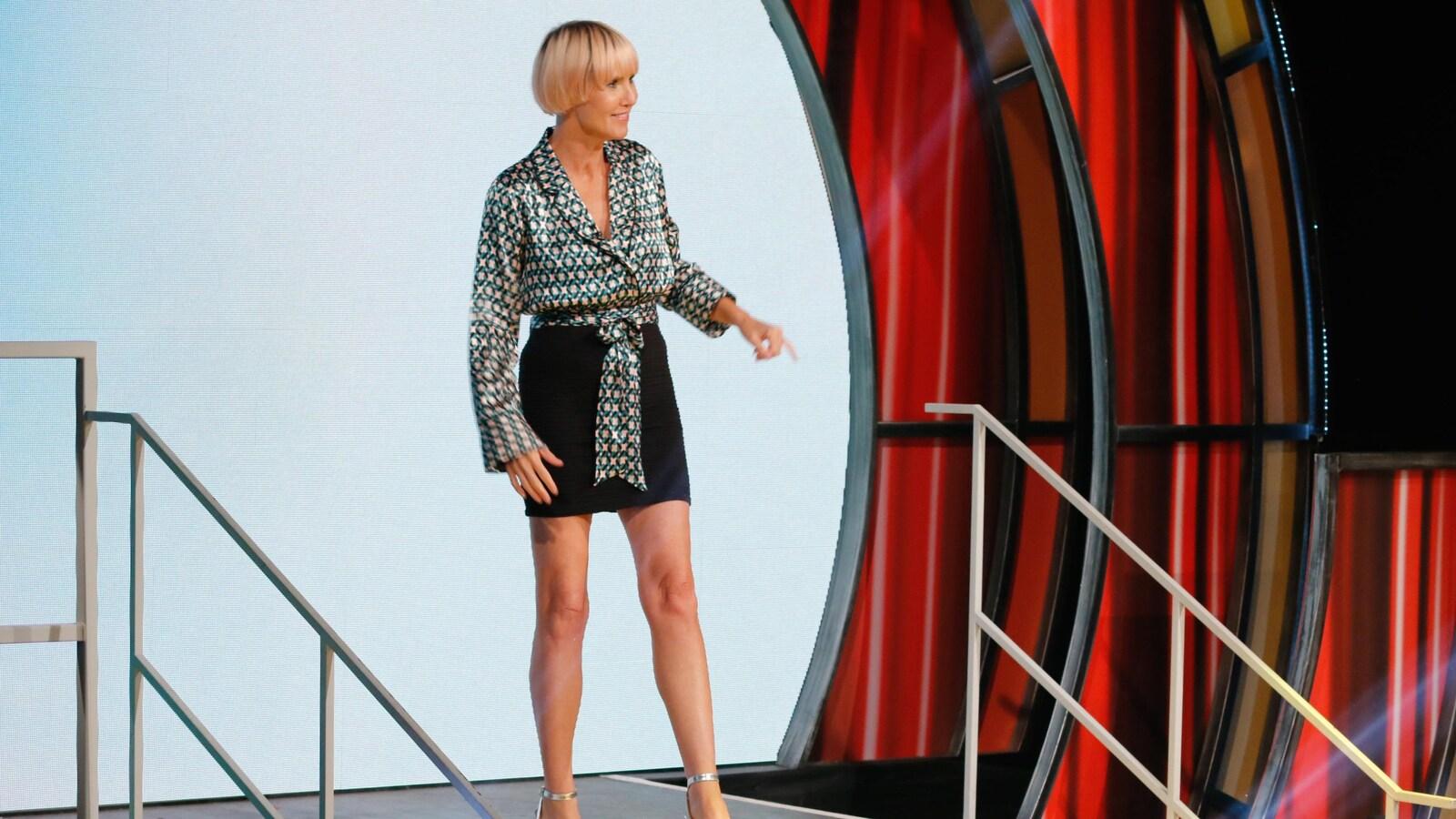 Pénélope porte une minijupe noire et une chemise à motifs et à manches longues.