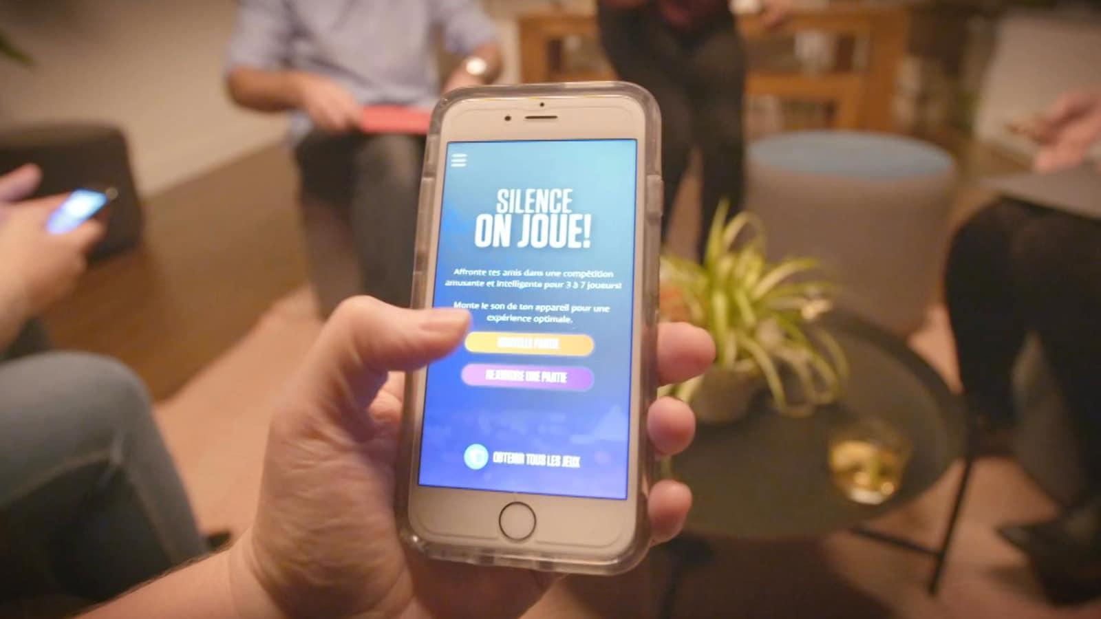 Une personne tient un téléphone qui affiche l'application.