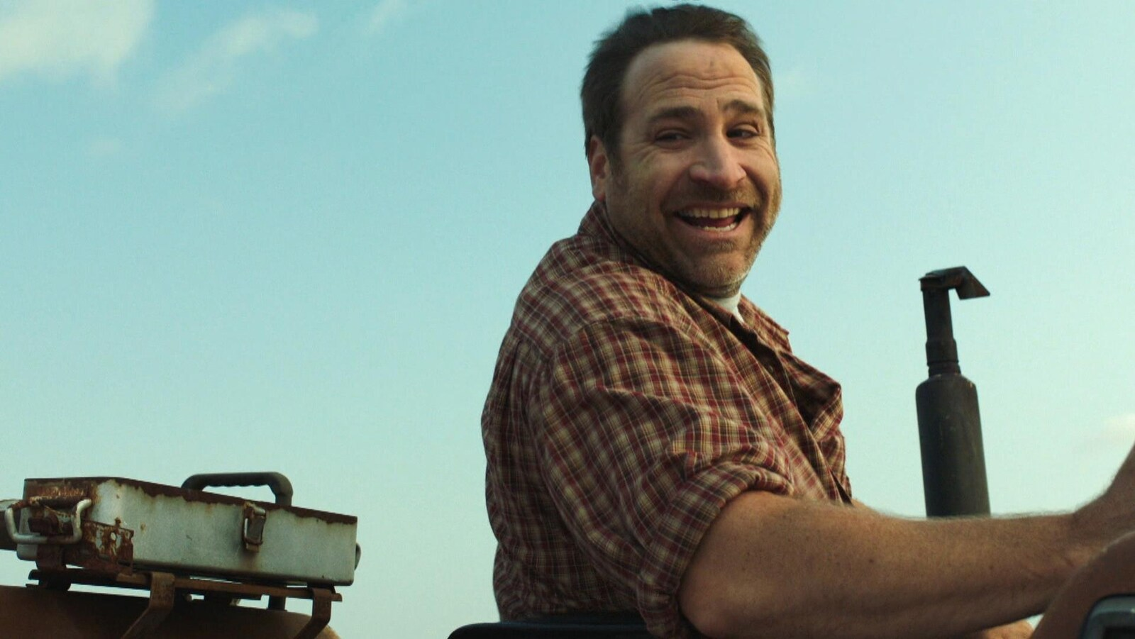Un comédien sourit sur un camion à la ferme.