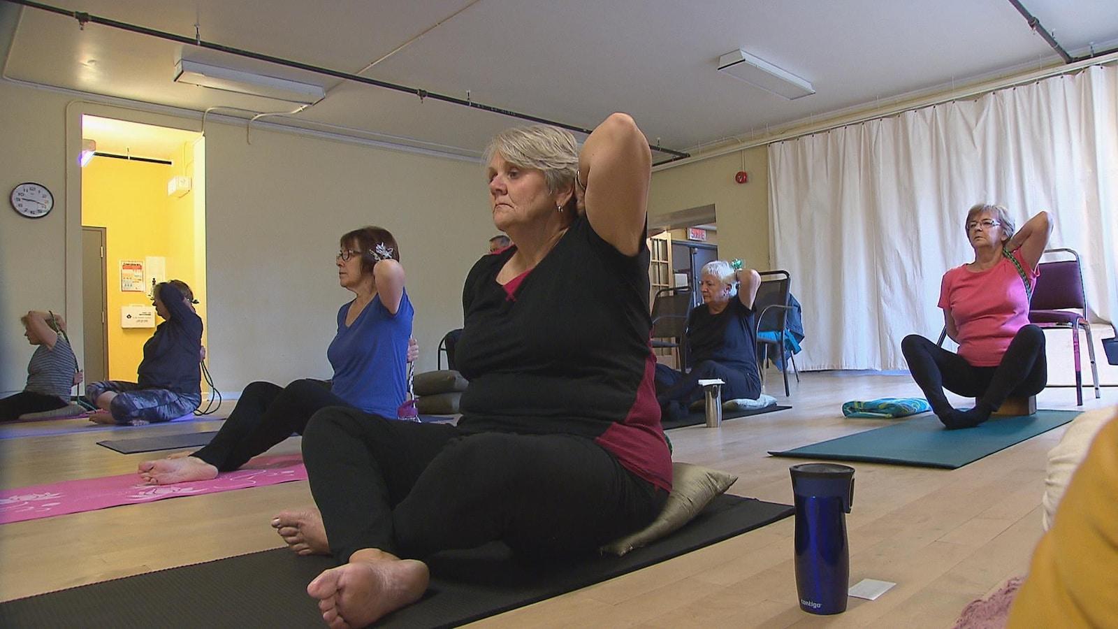 Des aînés de l'Université du 3e âge à une session de yoga.